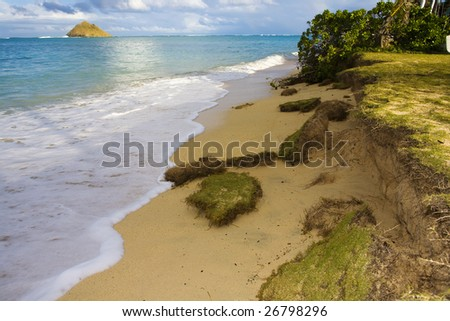 the front yard of a beach house is being washed away by rising sea levels - stock photo