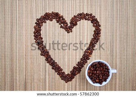 The full cup of coffee near the coffee beans in the shape of the heart - stock photo
