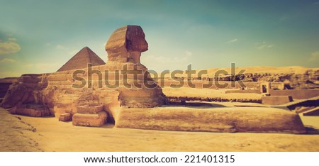 The full profile of the Great Sphinx with the pyramid  in the background in Giza. Egypt. Filtered image:cross processed lomo effect.  - stock photo
