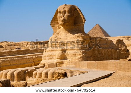 The full profile of the Great Sphinx with the pyramid of Menkaure in the background in Giza, Egypt - stock photo