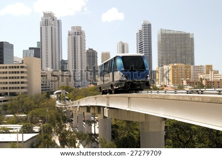 The fully automated Miami downtown train system with the city in the background - stock photo