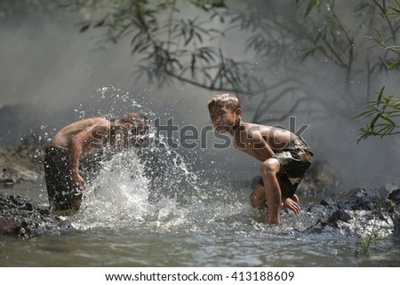 The fun of playing at the river . - stock photo