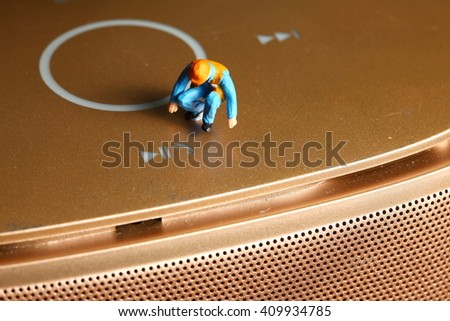 The functional touch button of the loudspeaker with maintenance miniature figure plastic model represent the speaker sound device and service concept related idea. - stock photo