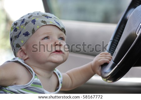 The funny baby holds a wheel in a car - stock photo