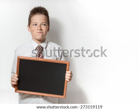 The funny pawky schoolboy teenager shows the black empty chalkboard with place for text - stock photo