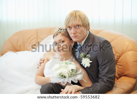 The future husband and the wife on a leather sofa in a solemn hall - stock photo
