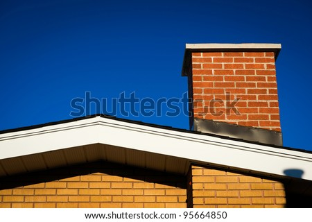 The Gable of a brick house with brick chimney in bright sunlight, against a deep blue sky. - stock photo