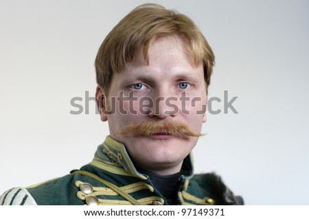 The gallant russian hussar posing on the wall background - stock photo