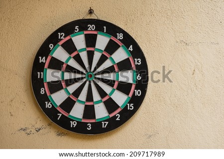 The game of darts, target on wall in a garden - stock photo