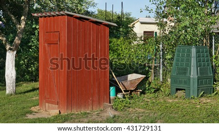 The garden toilet in rustic style is made of pine brown boards. Nearby there is a plastic container for processing of weeds in compost. Early summer morning