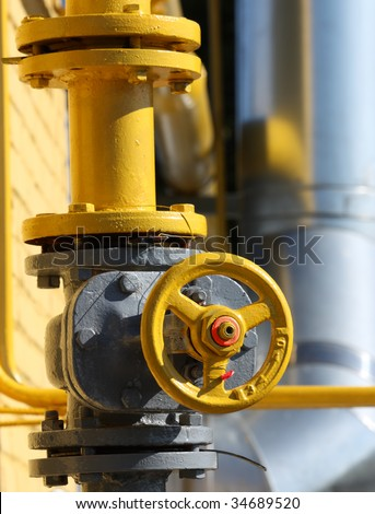 The gas gate, yellow valve and yellow pipes. - stock photo