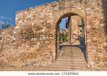 the gate in the medieval city walls with a narrow alley on the interior of the little town Montefalco, Umbtia , Italy - stock photo