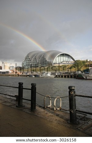 the gateshead sage music hall captured with a rainbow behind it - stock photo