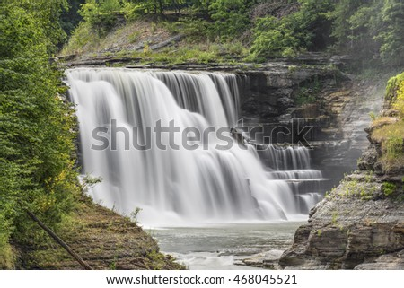 The Genesee River pours over the rocky ledges of Lower Falls, a waterfall in New York's Letchworth State Park.