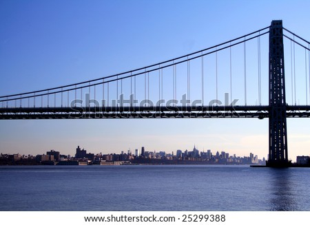 The George Washington Bridge crosses over the Hudson River from New Jersey to The Bronx, New York. New York Skyline in background. - stock photo