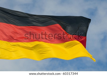 The German flag flying against a partly cloudy sky.