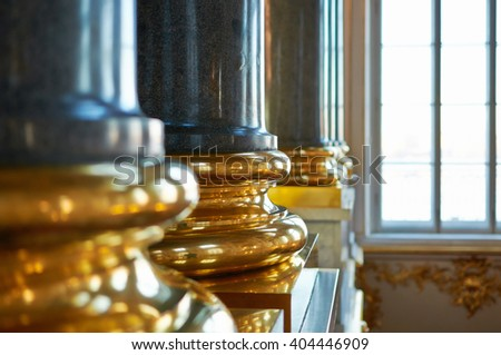 The gilded basis of a granite column lit with light from a window