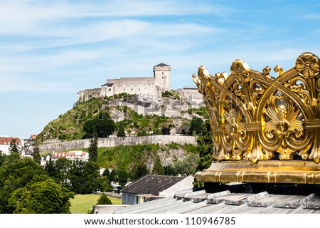 the gilded crown of the lourdes basilica and walls of the castle in the distance - stock photo