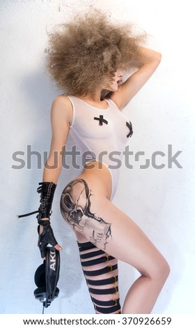 The girl - a DJ with a painted tattoo with headphones in hand, standing near a white wall - stock photo