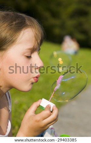 The girl and a soap bubble in sunny day