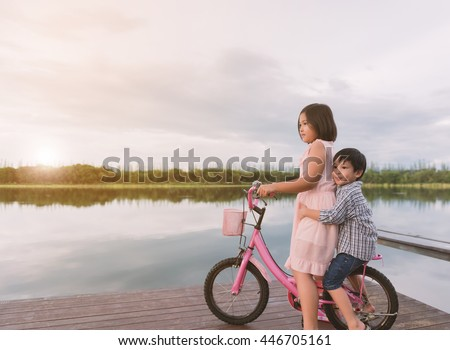 The girl and a younger man sitting on a bicycle looking nature.
