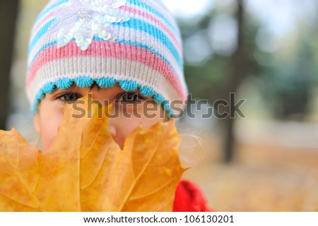 The girl and autumn leaf. A sight because of big yellow leaf. Focus on eye - stock photo