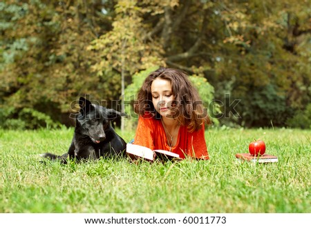 The girl and dog lying on a grass in park - stock photo