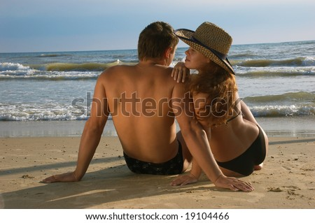 The girl and man sit on a coast of the sea - stock photo