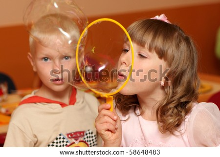 The girl and the boy blow bubbles indoor - stock photo
