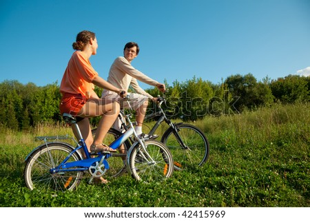 The girl and the man go for a drive on bicycles in a sunny day - stock photo