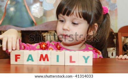The girl and toy cubes. The child collecting a word family from cubes. - stock photo