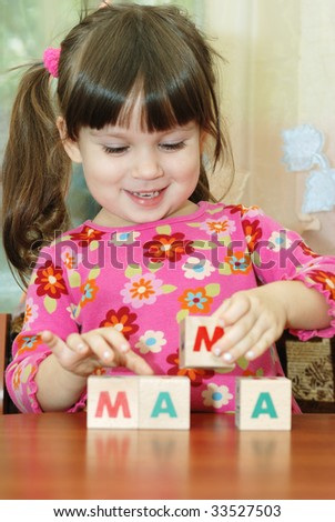 The girl and toy cubes. The child collecting a word mama from cubes. - stock photo