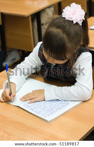 The girl at a lesson sits at a school desk and writes the text to writing-books - stock photo
