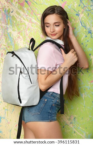 The girl at a wall color looks on your backpack behind - stock photo