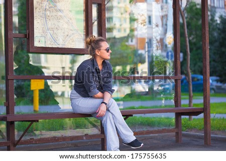 The girl at the bus stop in sunglasses . Photographing outdoors. - stock photo
