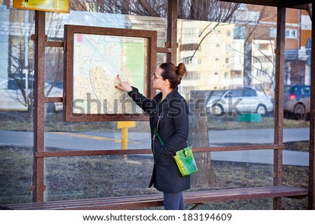 The girl at the bus stop looking at the route map. - stock photo