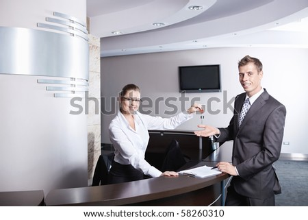 The girl at the reception gave the key businessman - stock photo