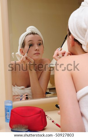 The girl before a mirror with make-up - stock photo