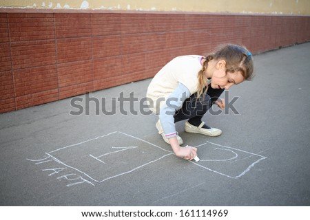 The girl begins to draw hopscotch on the pavement on the street - stock photo