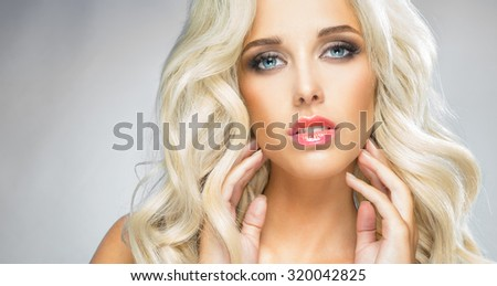 The girl - blonde feels the face with his hands