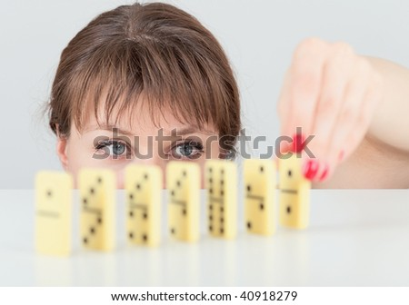 The girl builds a line of dominoes counters close up