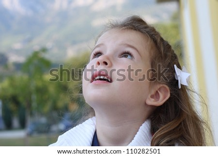 The girl child is looking up - stock photo