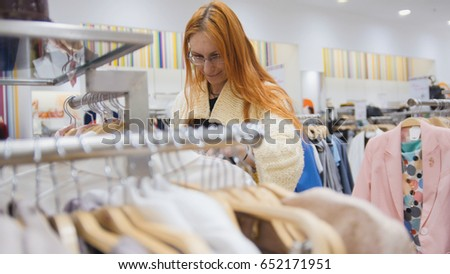 The girl chooses an outfit among a variety of women's clothes