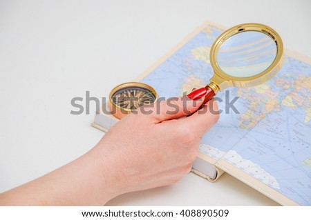 The girl considers the world map through a magnifying glass. Search of a route of travel. Explaining the ground. - stock photo