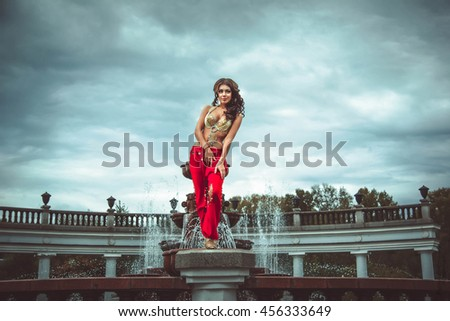 the girl dancer is standing at the fountain in the suit