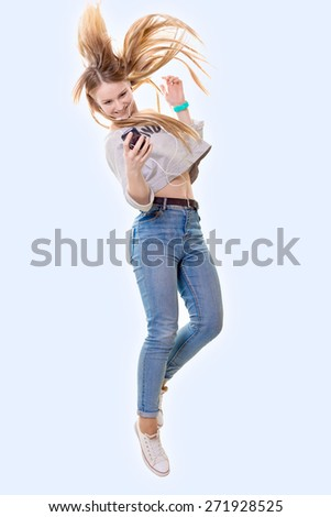 The girl dances and looks in phone - stock photo