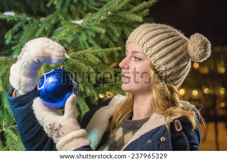 The girl decorates a fur-tree - stock photo