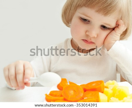 The girl does not eat the vegetables. - stock photo
