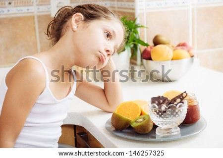 the girl does not like healthy breakfast. She wants to eat cakes - stock photo