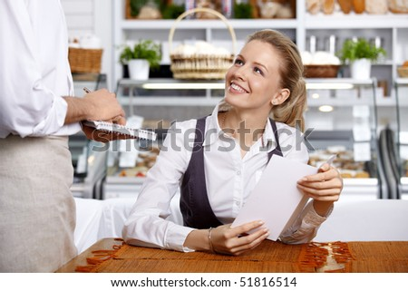 The girl does the order to the waiter in cafe - stock photo
